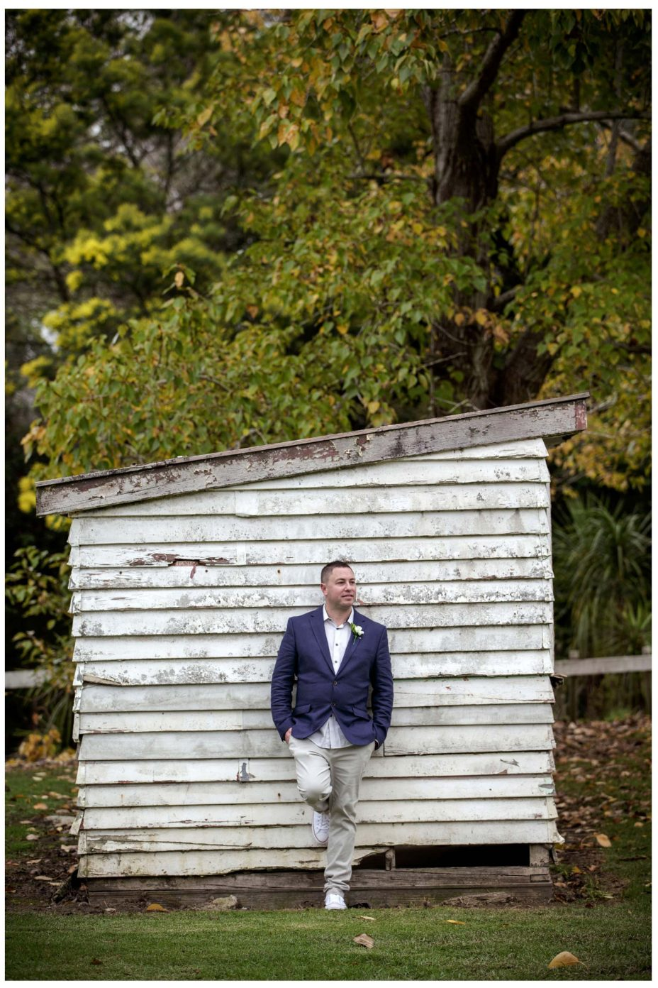 Wedding groom leans against rustic shed in Puhoi Village Auckland
