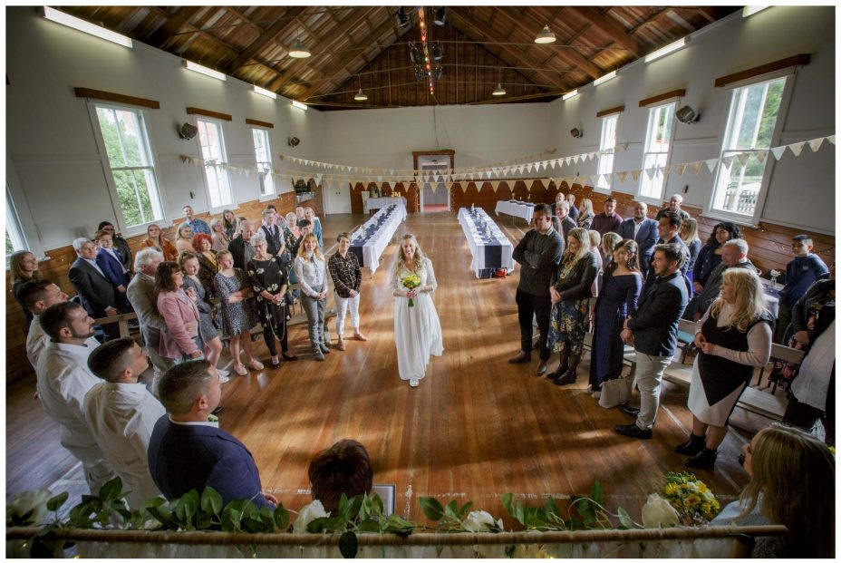 Bride in white dress enters Puhoi Village Hall