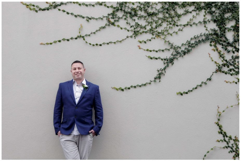Bridegroom in blue blazer against ivy wall