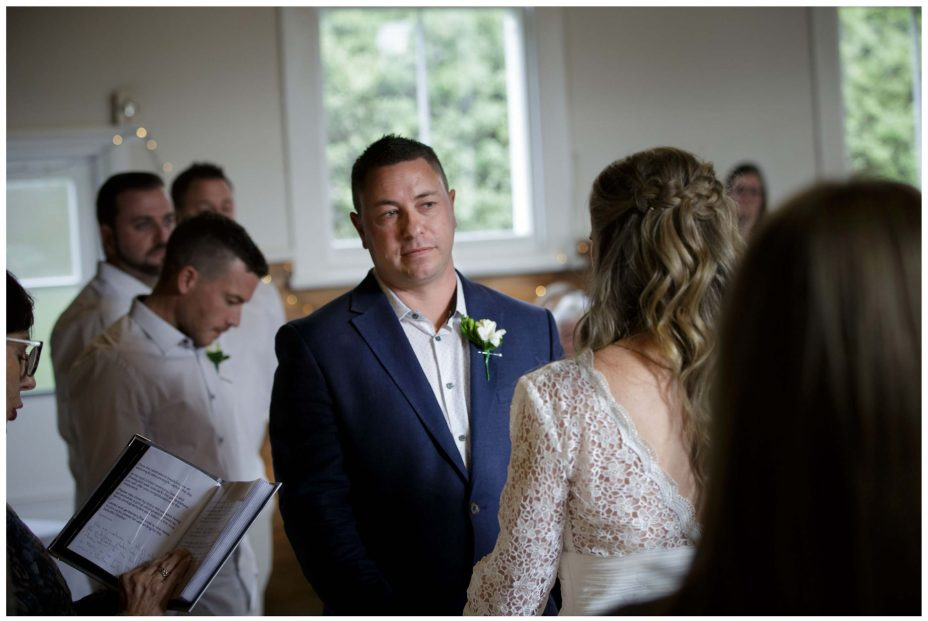 Groom looks lovingly at bride in wedding ceremony at Puhoi Village Hall