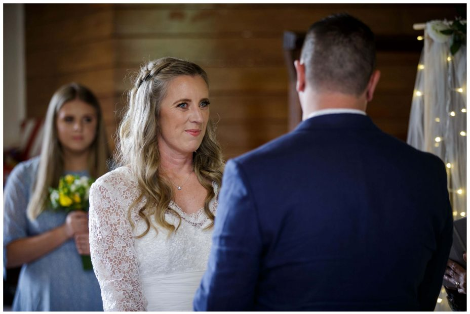 Bride looks lovingly at groom in wedding ceremony at Puhoi Village Hall