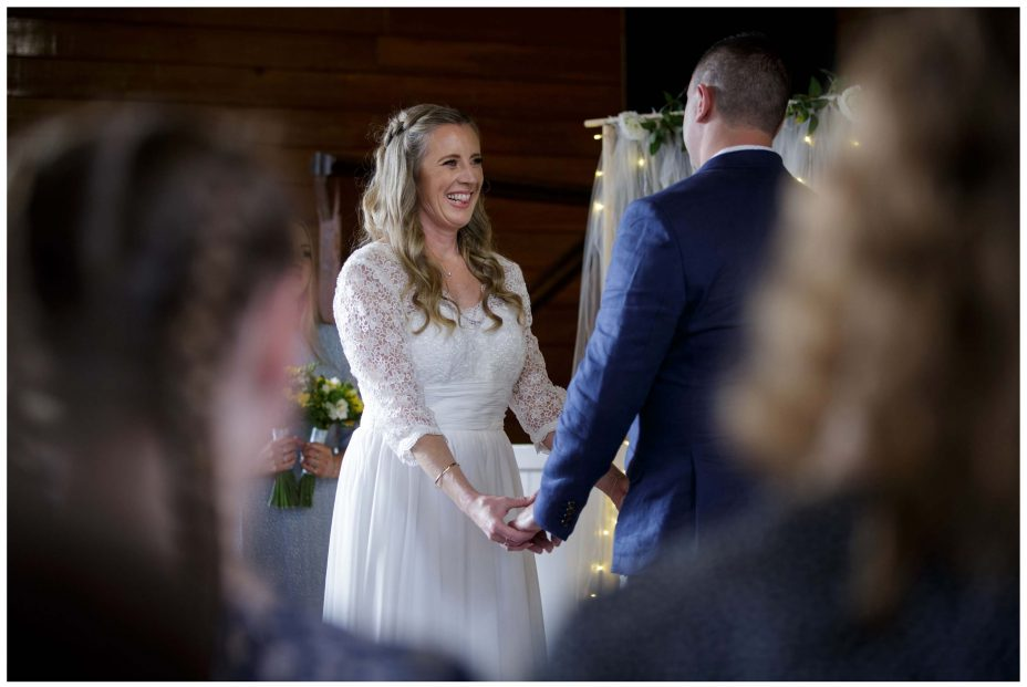 Bride smiles lovingly at groom in wedding ceremony at Puhoi Village Hall
