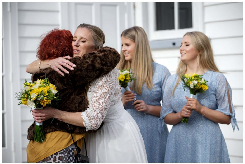 Bride hugs wedding guest outside Puhoi Village Hall