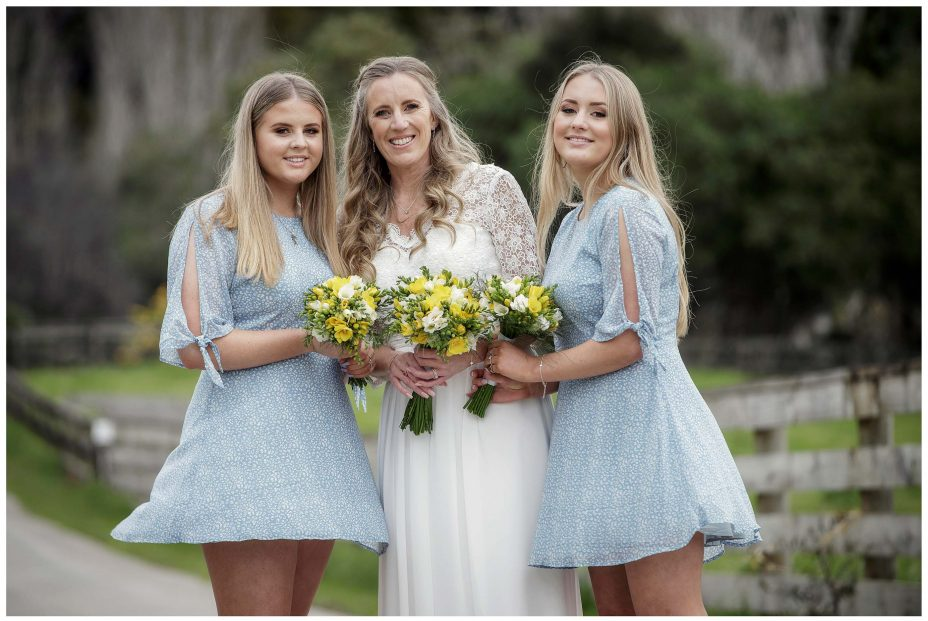 Bride in white dress with two daughters as wind lifts their dresses