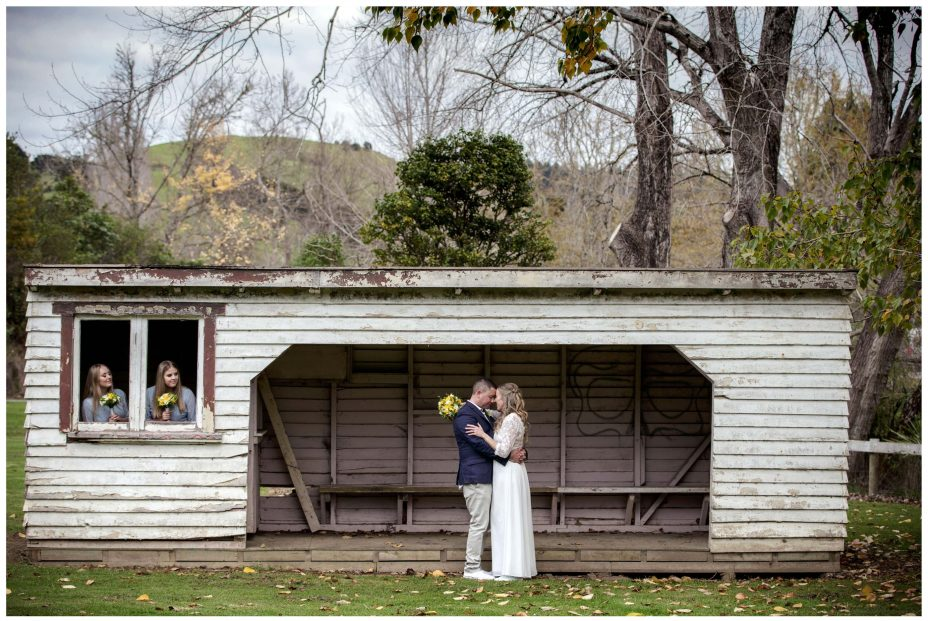 Bride and Groom pose by rustic shed puhoi village Auckland