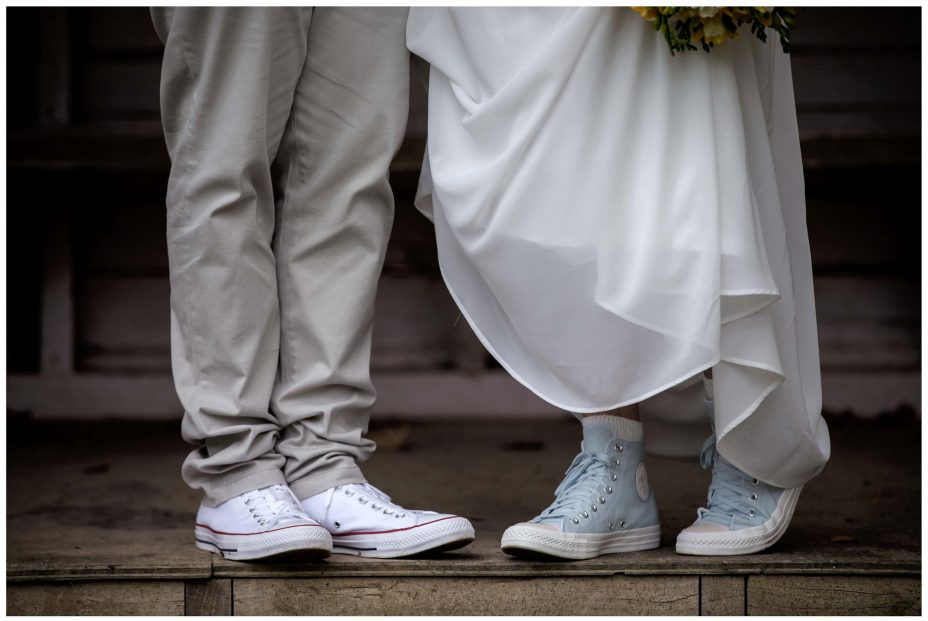 Bride and groom show off their Converse wedding shoes