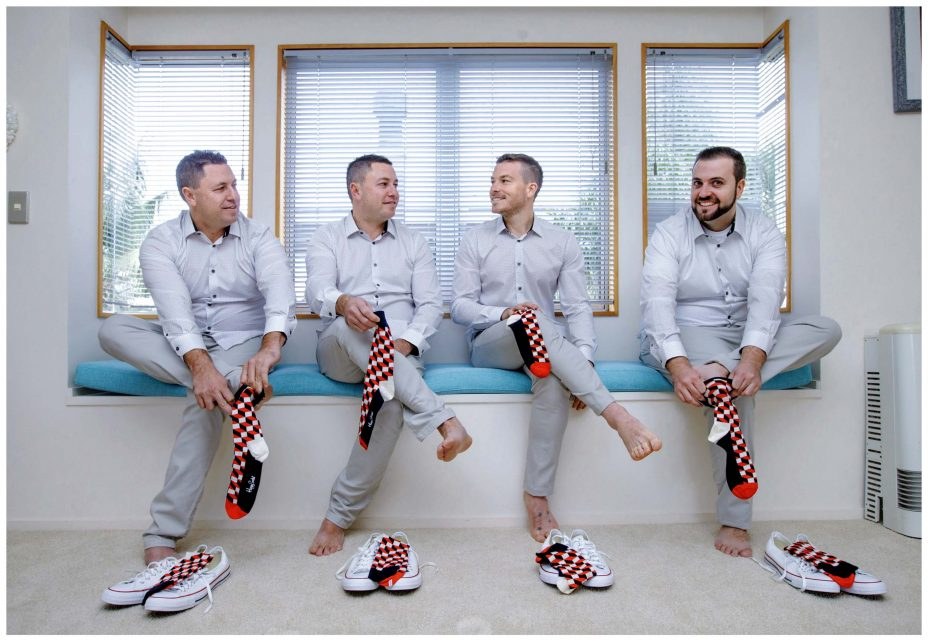 Groomsmen get ready for wedding wearing matching socks