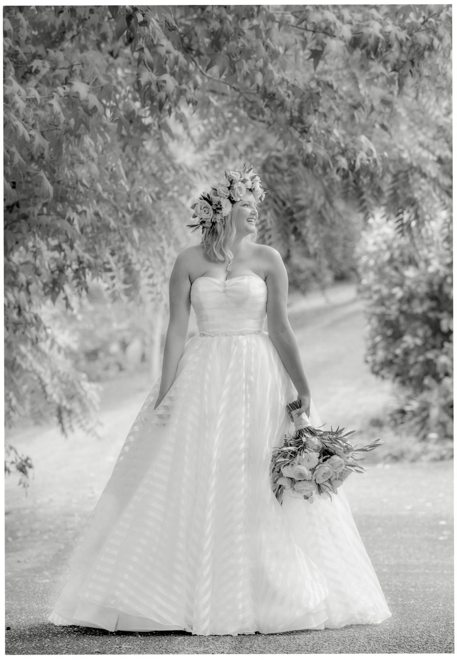 Black and white portrait of bride in full length white wedding dress from Astra Bridal. Flower crown and bouquet in hand.