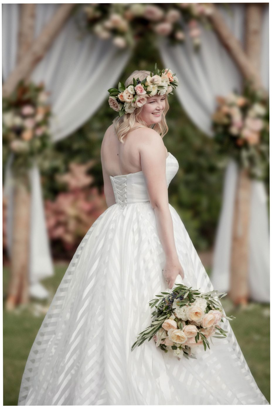 Auckland bride wearing flower crown and holding her wedding bouquet infront of her flower arch