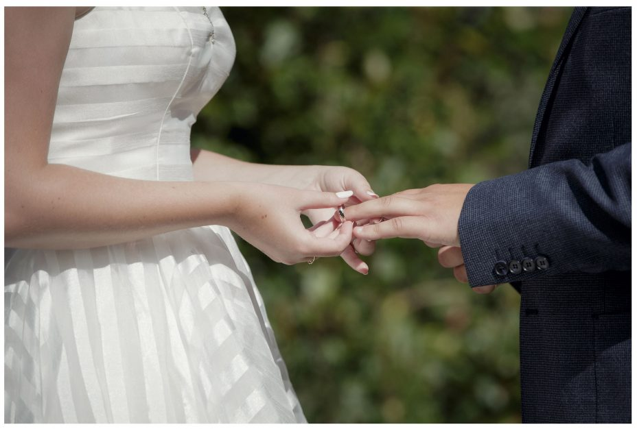 Close up photo of bride placing wedding ring on grooms finger as they make their vows.
