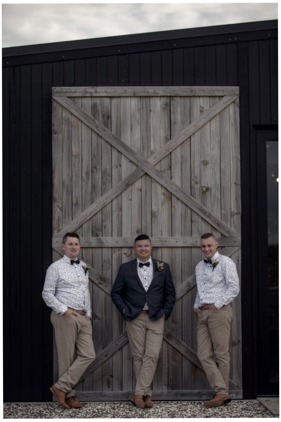 Groom and groomsmen lean against the large wooden doors of The Barn wedding reception venue at The Hunting Lodge Winery