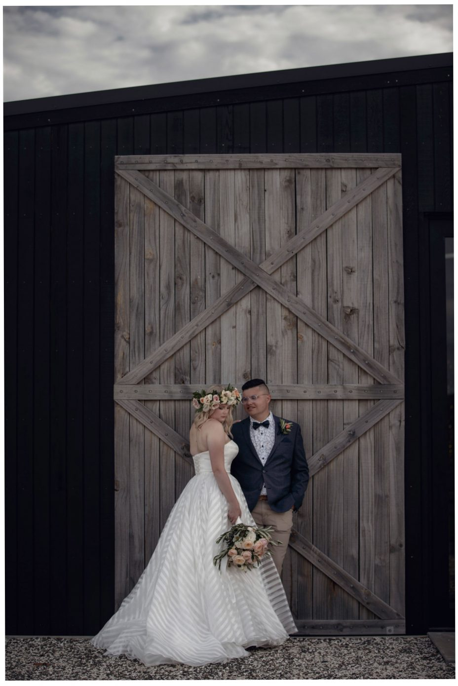 Bride and groom lean against the large wooden doors of The Barn wedding reception venue at The Hunting Lodge Winery