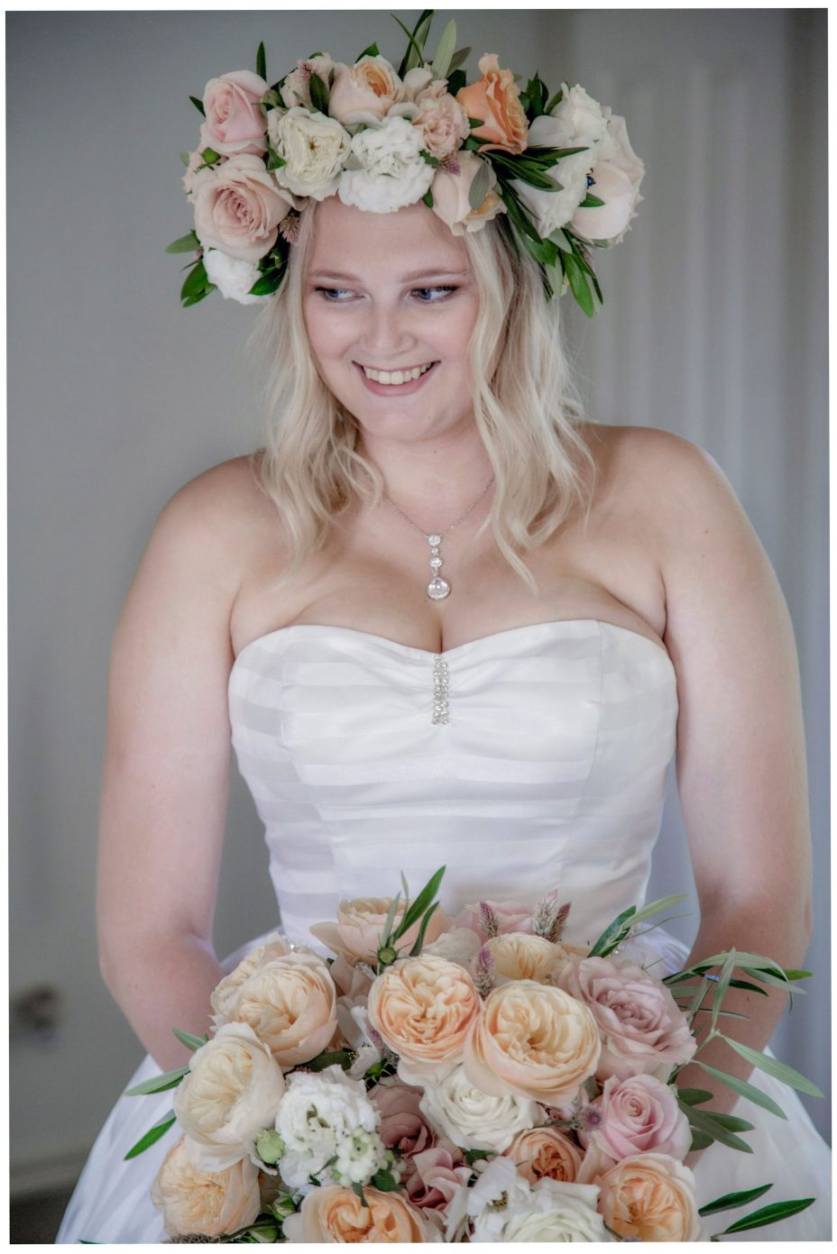 Portrait of blond haired bride wearing flower crown and carrying wedding bouquet