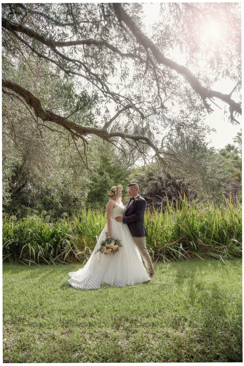 Bride and groom pose in the evening sunshine at The Hunting Lodge Winery Auckland