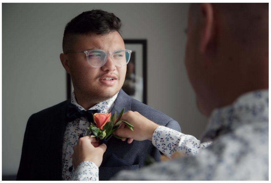 Best man adjust groom's buttonhole flower n