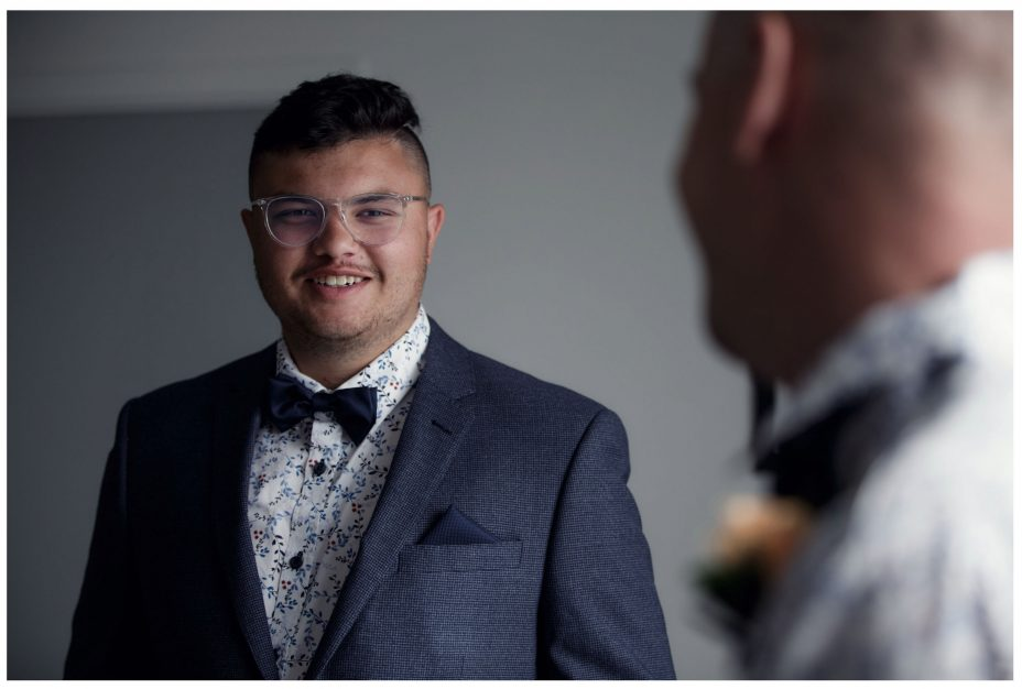 Bridegroom in suit and bow tie smiles to his bestman in conversation
