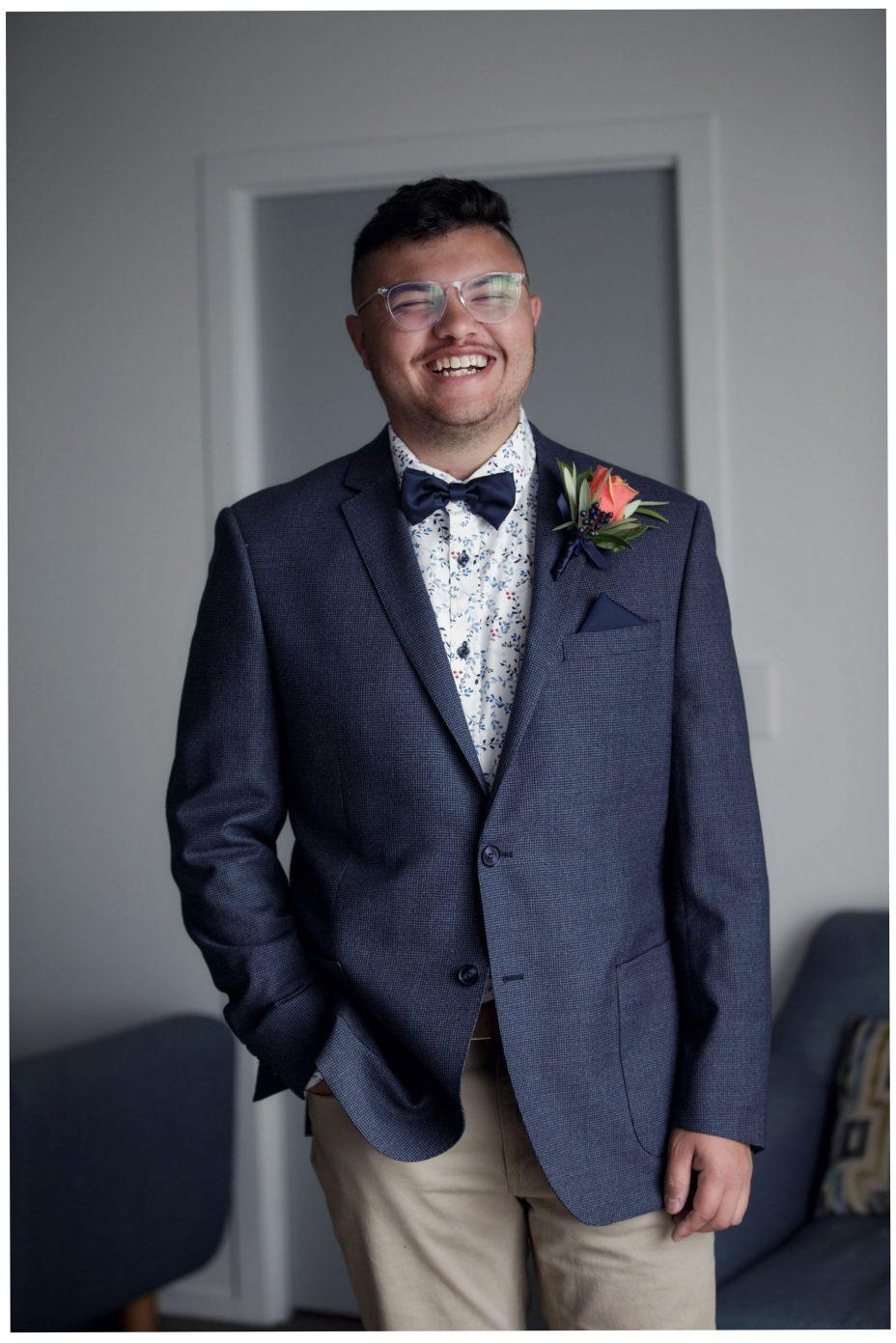Groom dressed for his wedding smiles full of joy.