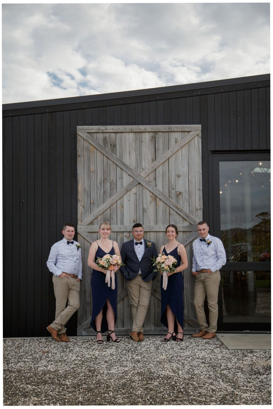 Bride groom and bridal party posed against the large wooden doors of The Barn wedding reception venue at The Hunting Lodge Winery