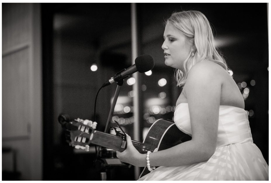 Bride plays guitar and sings her song to her groom at their wedding reception