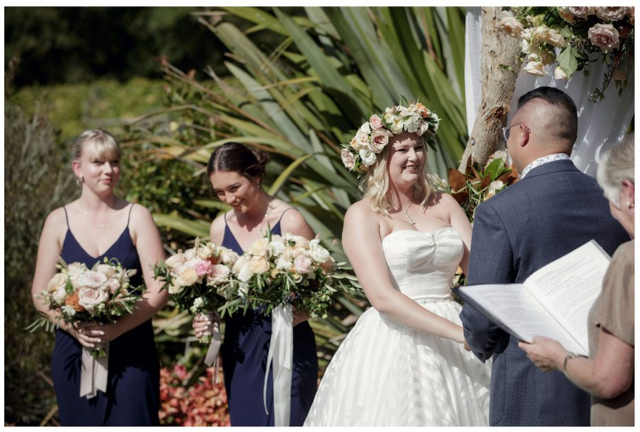 Bride wearing flower crown smiles at her groom during their wedding ceremony