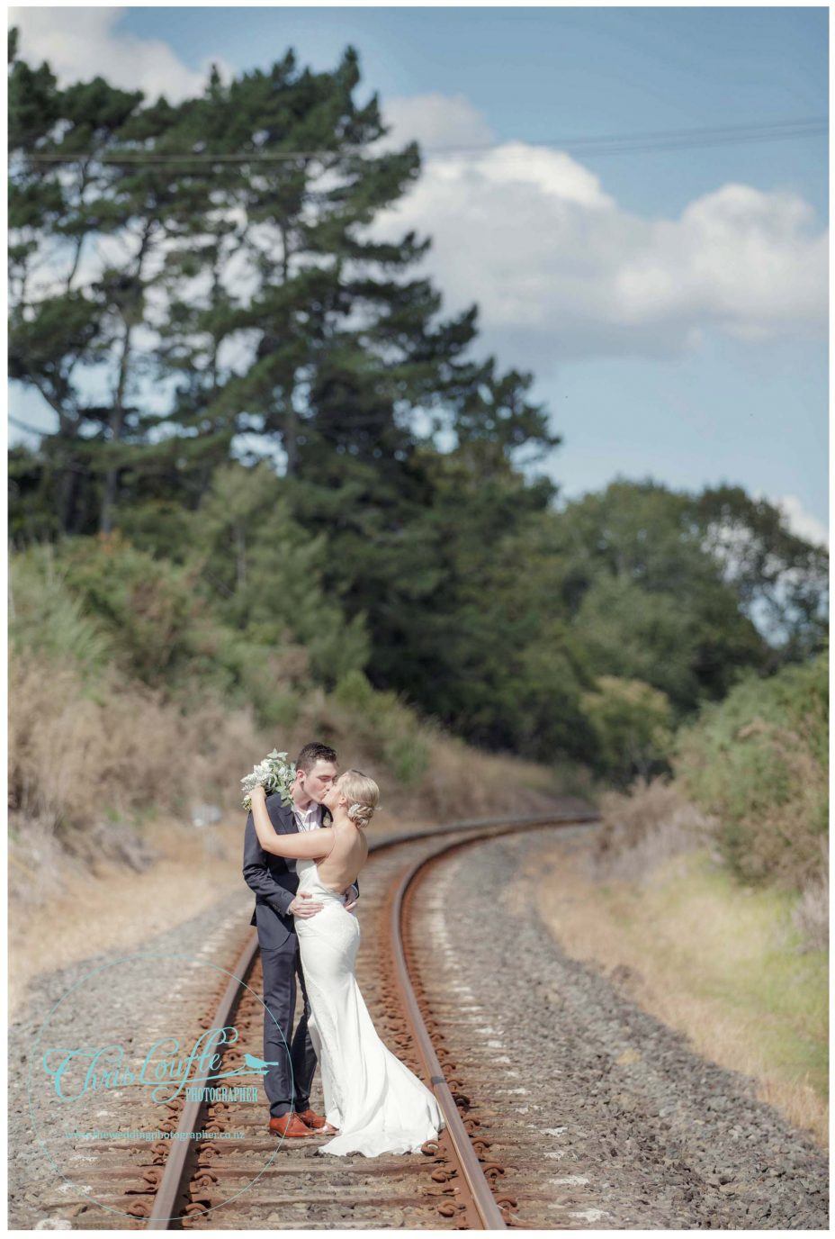 Bride and groom kiss for wedding photo on railway line Kumeu Auckland