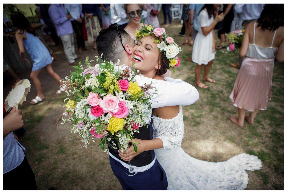 Smiling bride hugs guest, Flower crown, Leaf and Honey Wedding flowers, Kumeu Valley Estate garden outdoor wedding
