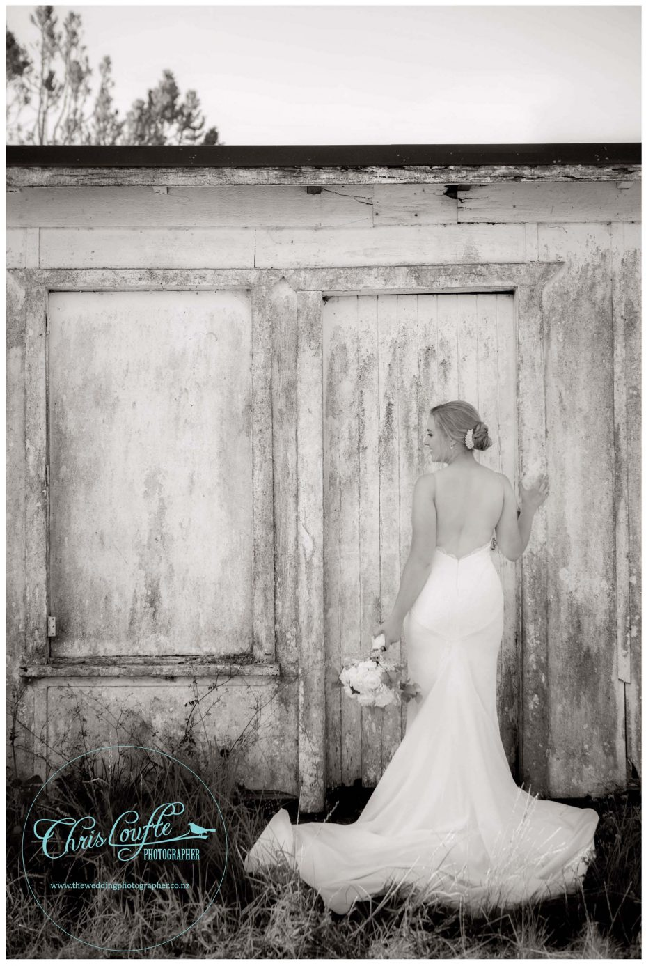 Bride in White backless weddding dress poses against rustic orchard outbuilding in Kumeu orchard, black and white photo