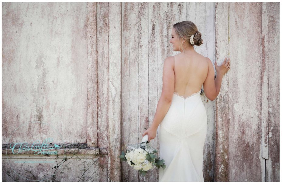Bride in White backless weddding dress poses against rustic orchard outbuilding in Kumeu orchard, Auckland.