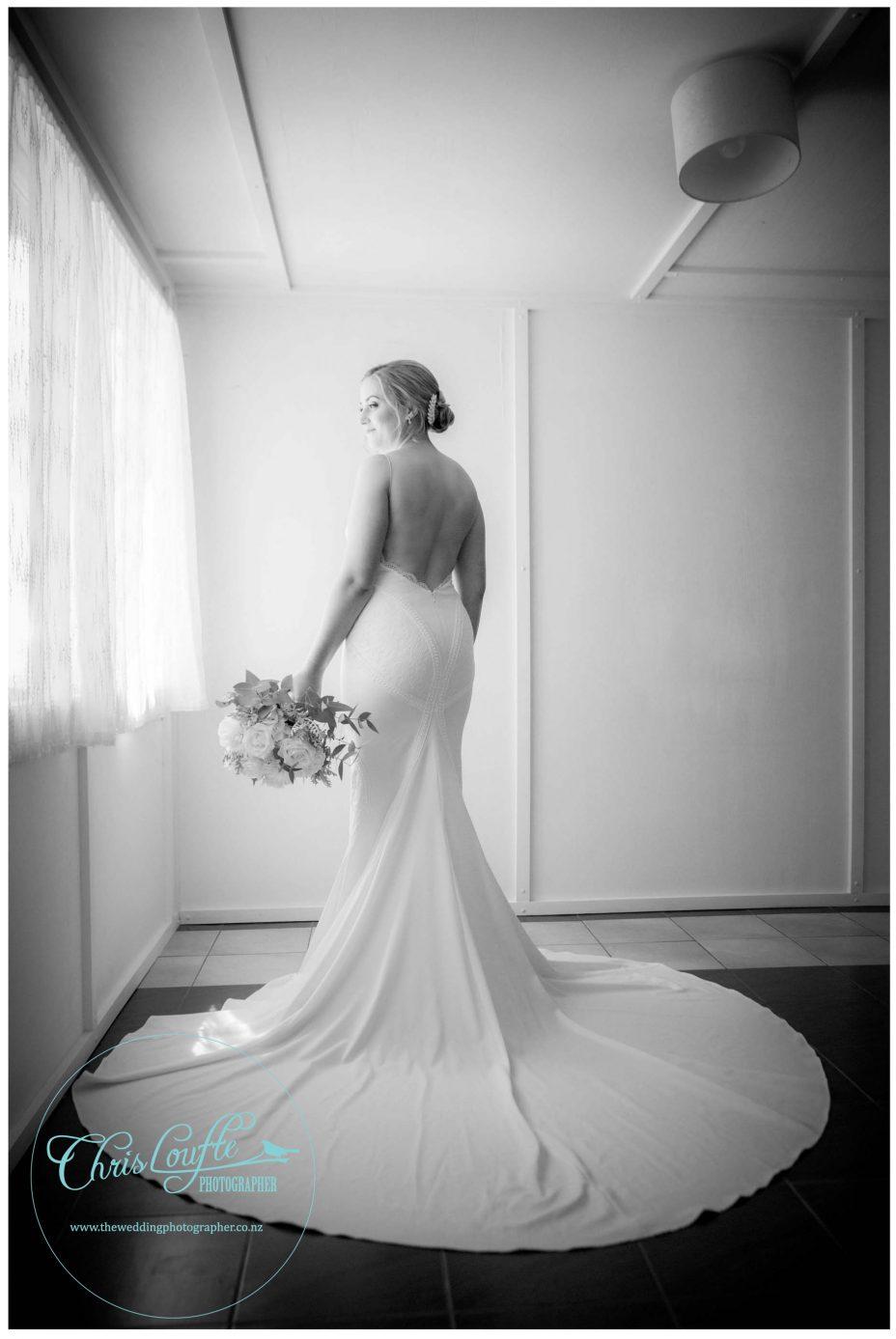 Bride in ivory backless wedding dress, wedding bouquet flowers, black and white photo, natural window light, Kumeu wedding