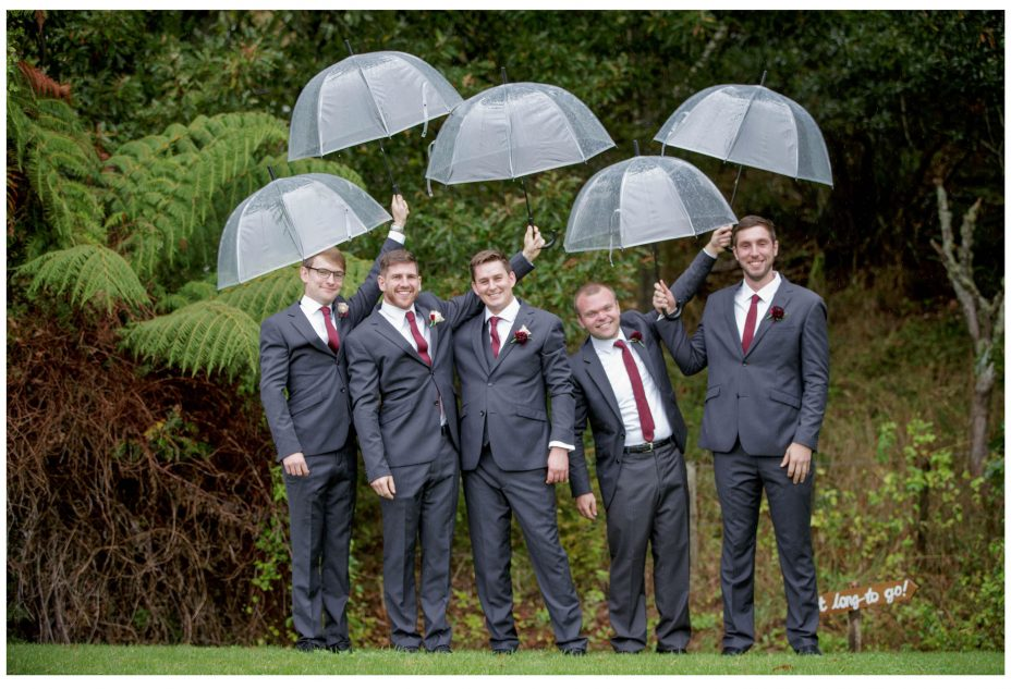 Wedding groom and groomsmen under clear umbrella's fun rainy wedding day photo