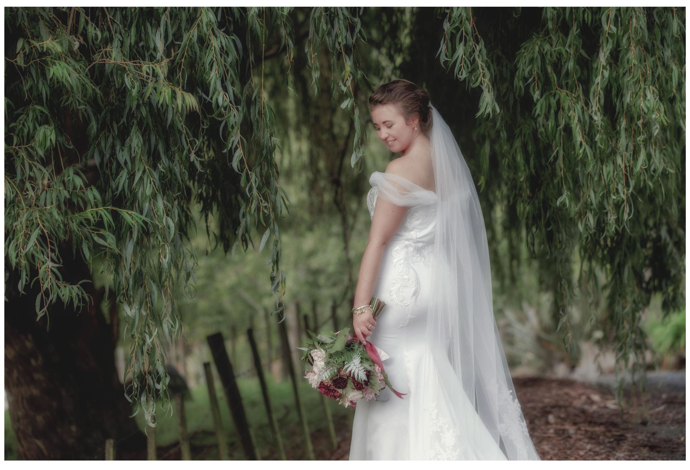 Bride in white wedding dress with flowers under willow tree in Kumeu