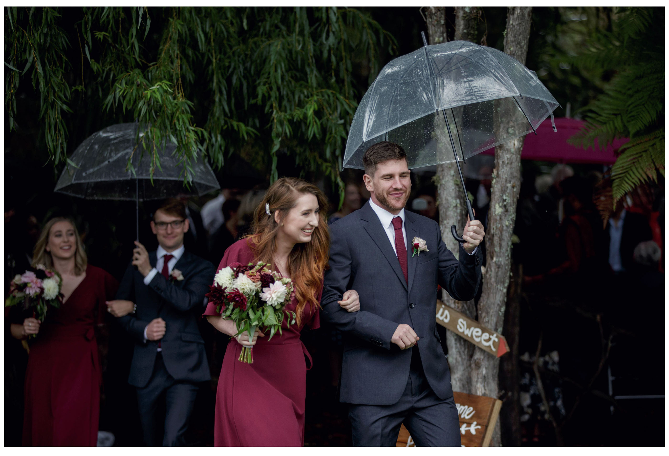 Bridesmaid and groomsman leave rainy wedding ceremony with clear umbrella