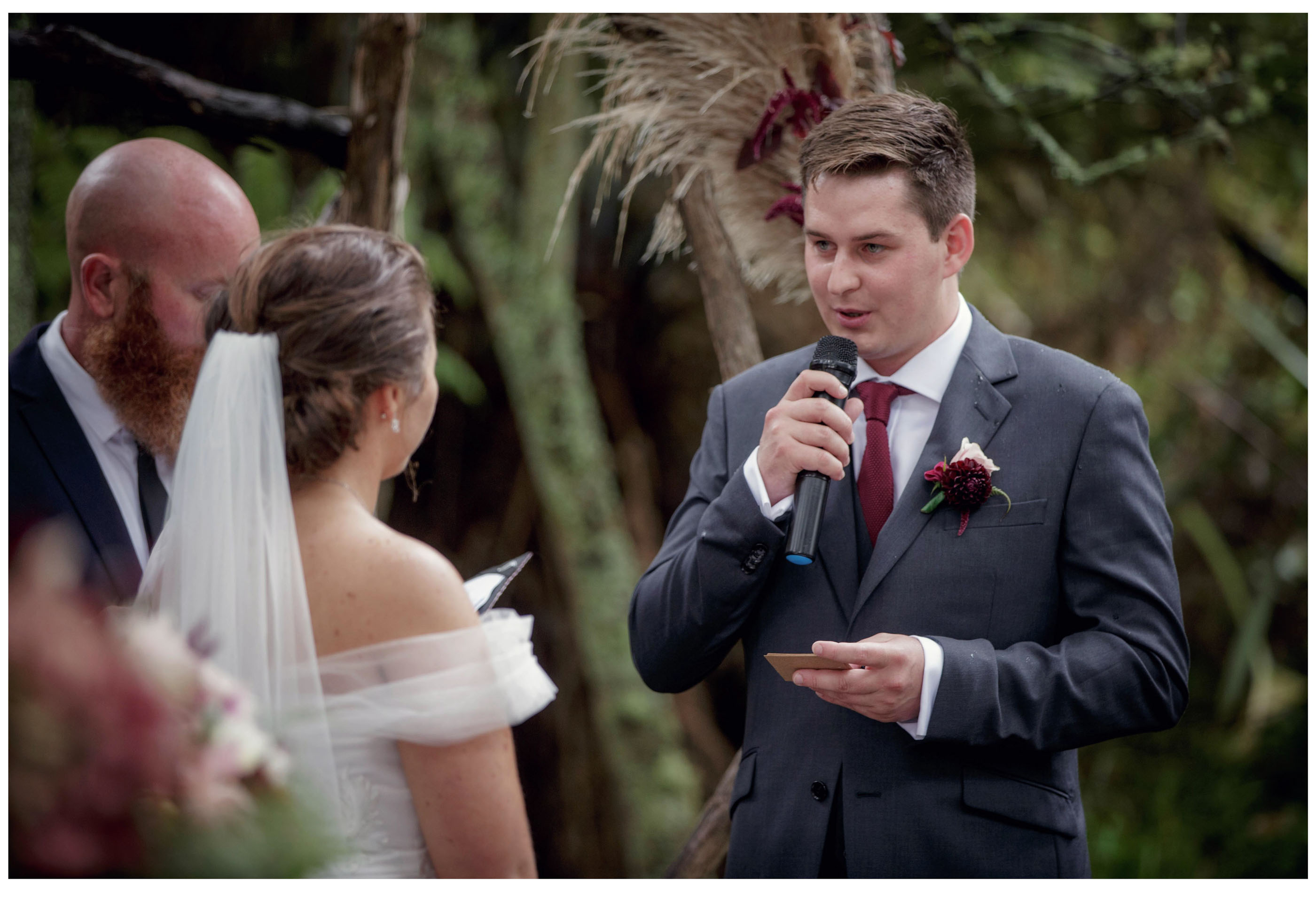 Groom makes wedding vows at outdoor woodland wedding Kumeu