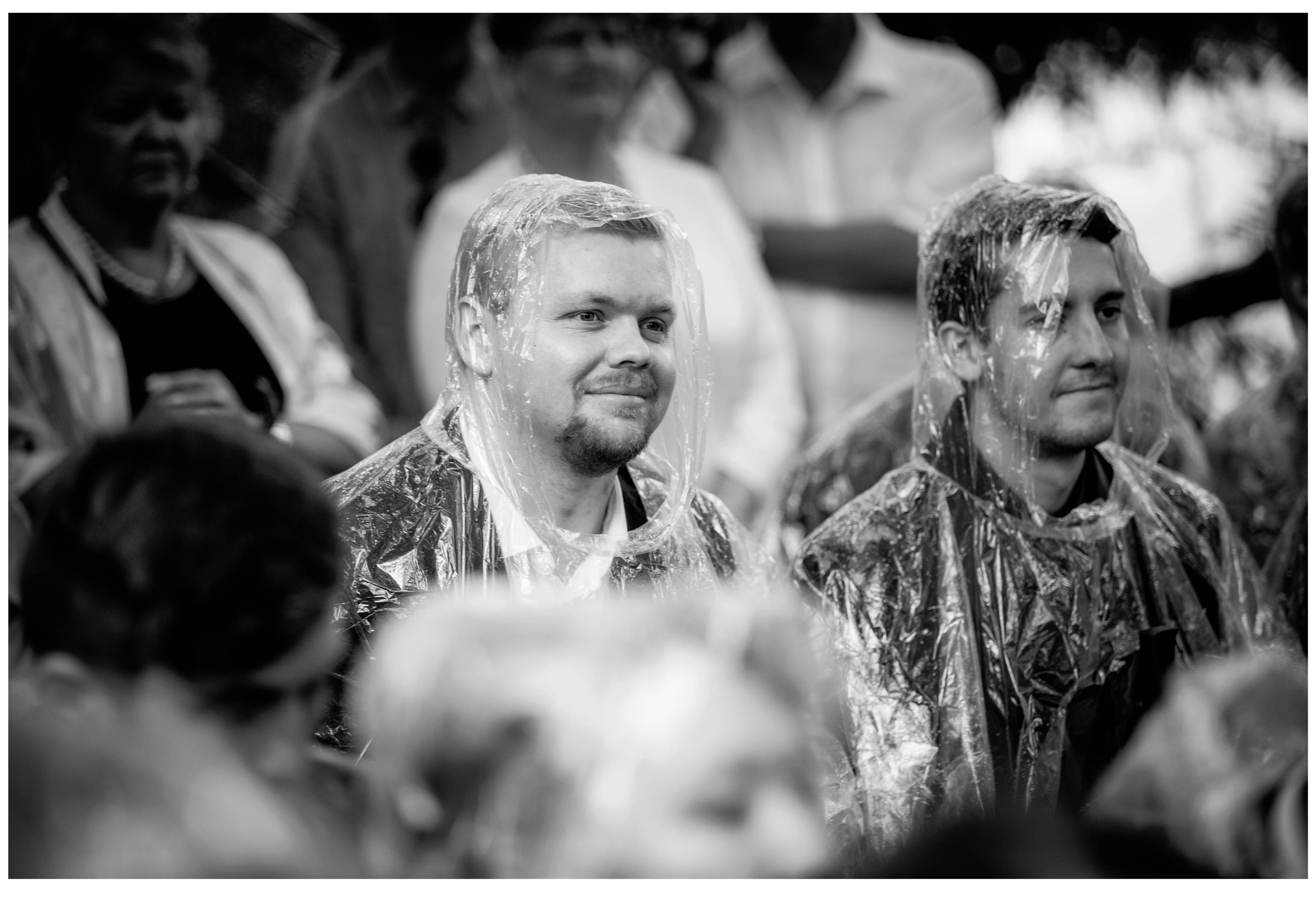 Wedding guests at outdoor Kumeu weding ceremony wearing rain poncho