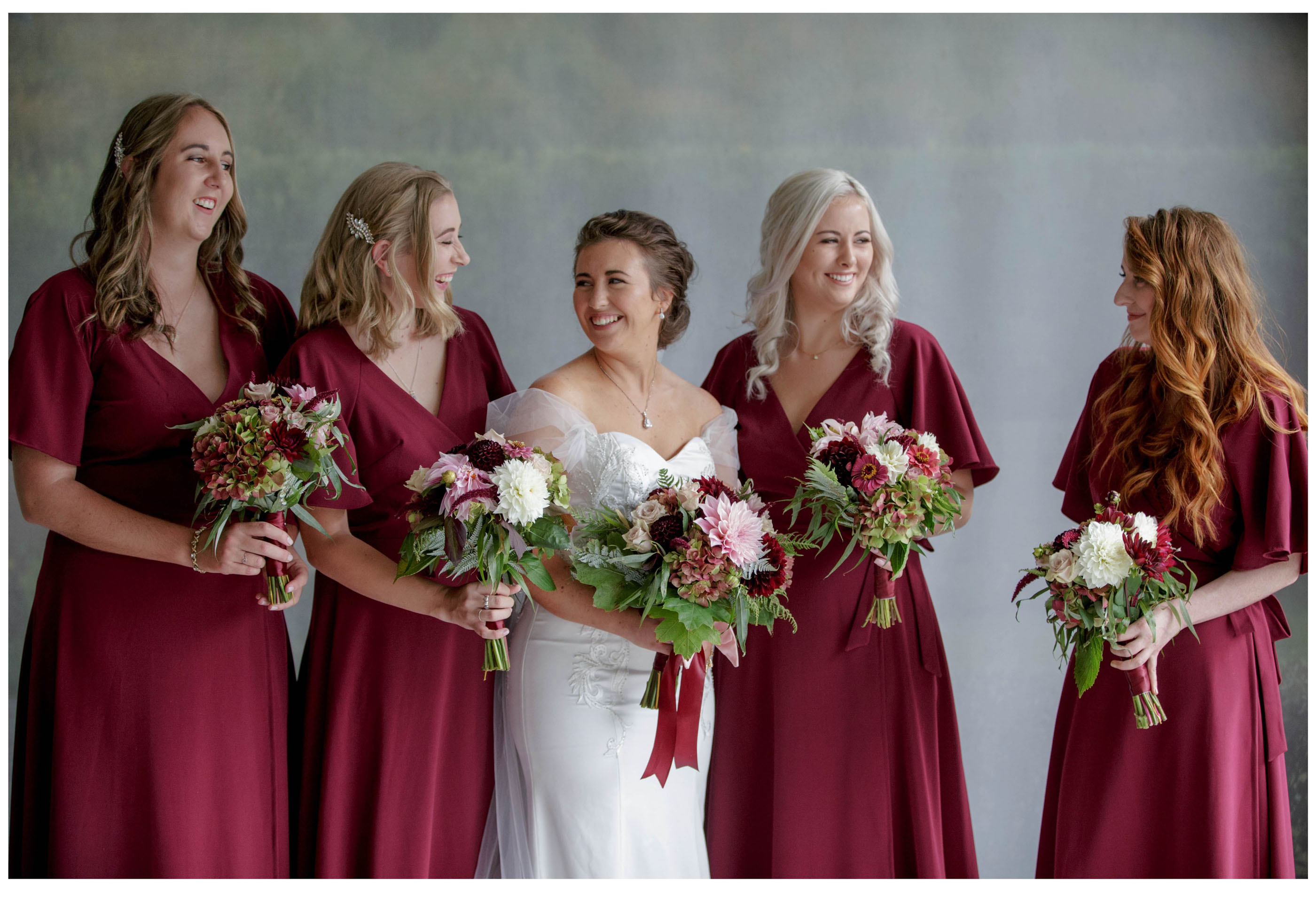 Bride laughts with bridesmaids at home in Kumeu