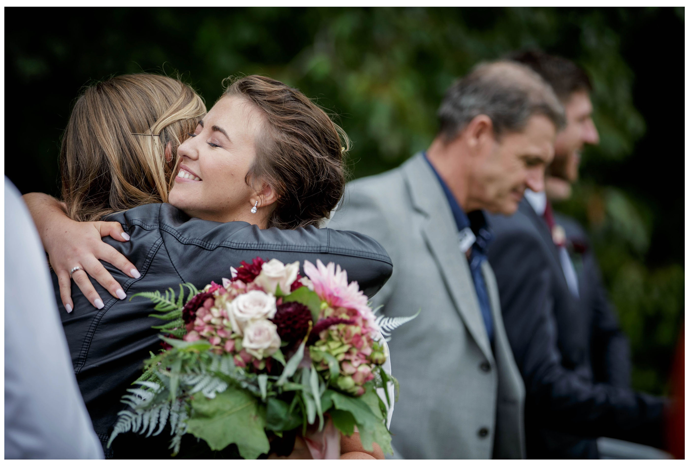 Bride hugs one of her wedding guests after her outdoor wedding ceremony in Kumeu
