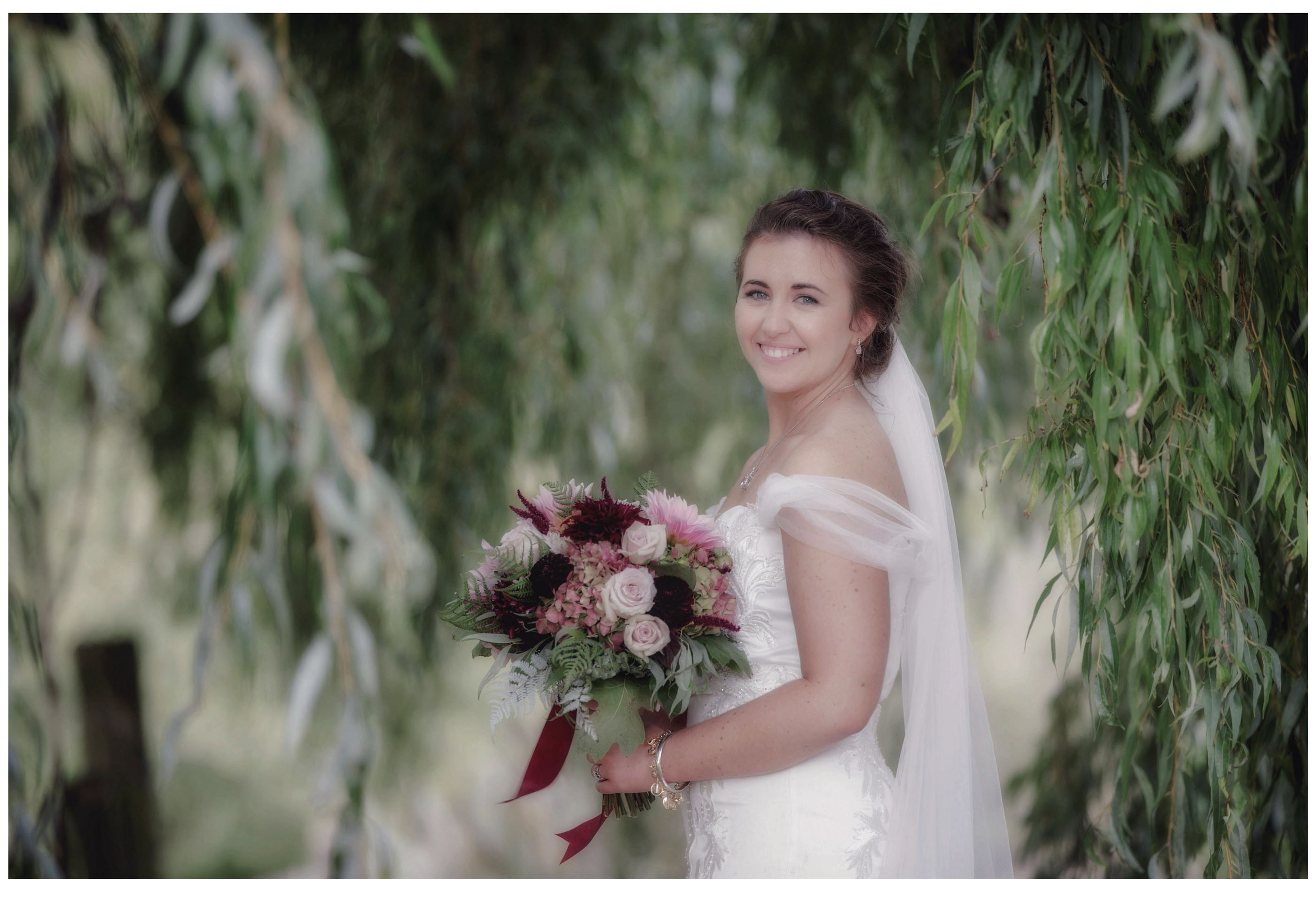 Bride in white lace top wedding dress with flowers under willow tree in Kumeu