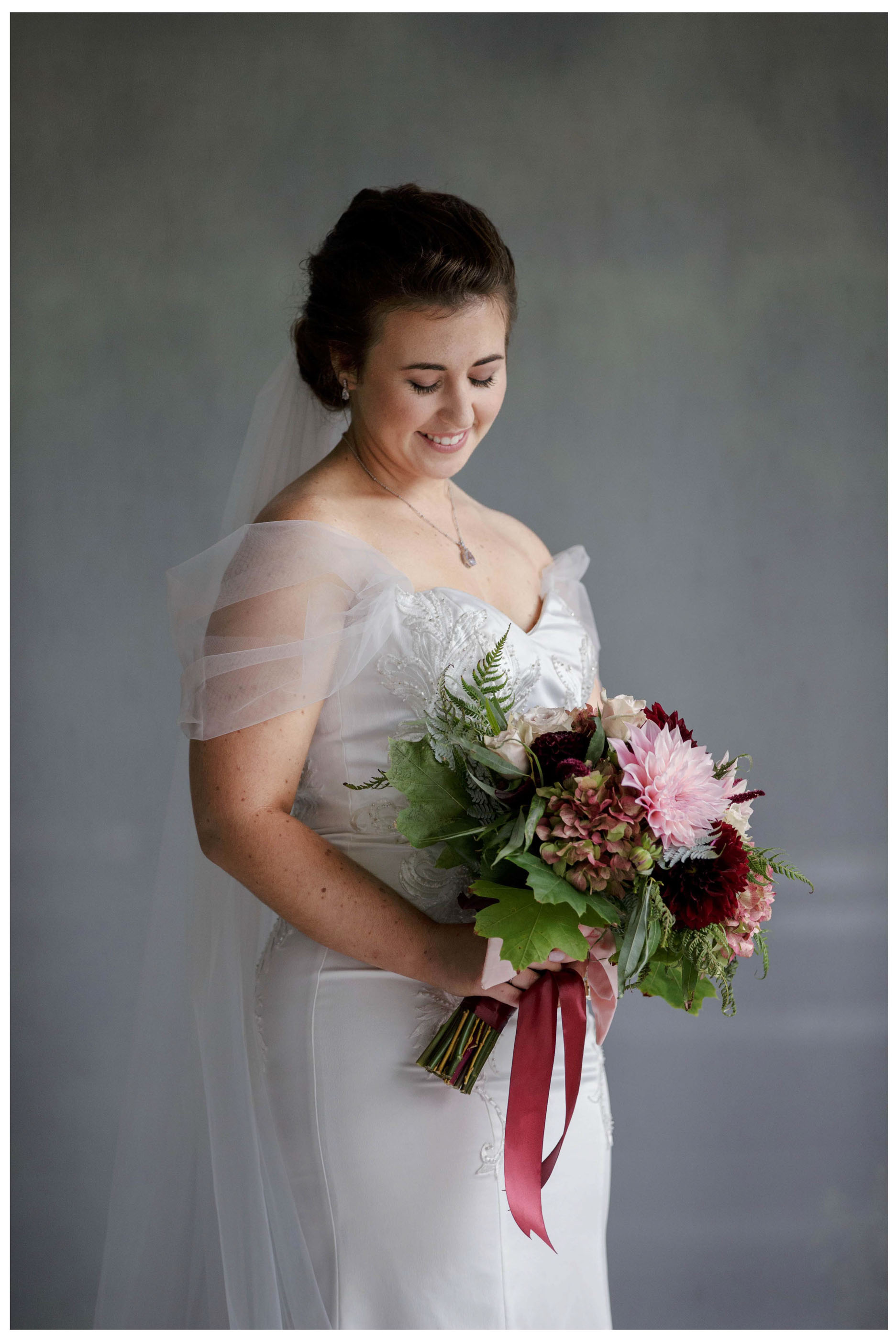 Kumeu Bride in lacetop wedding dress poses with her wedding bouquet , Laf and Honey