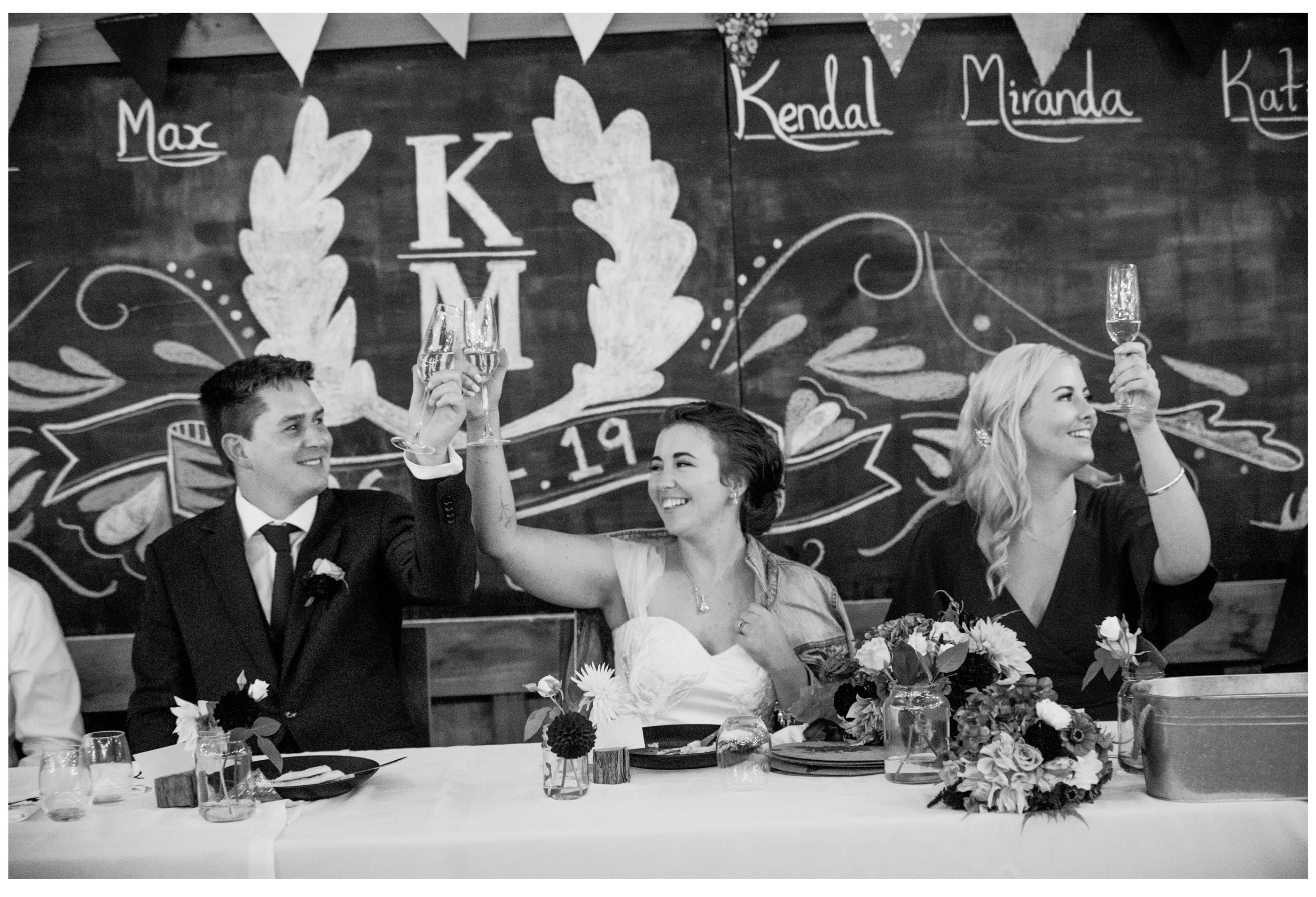 Bride and groom make champagne toast during their marquee weding reception in Kumeu