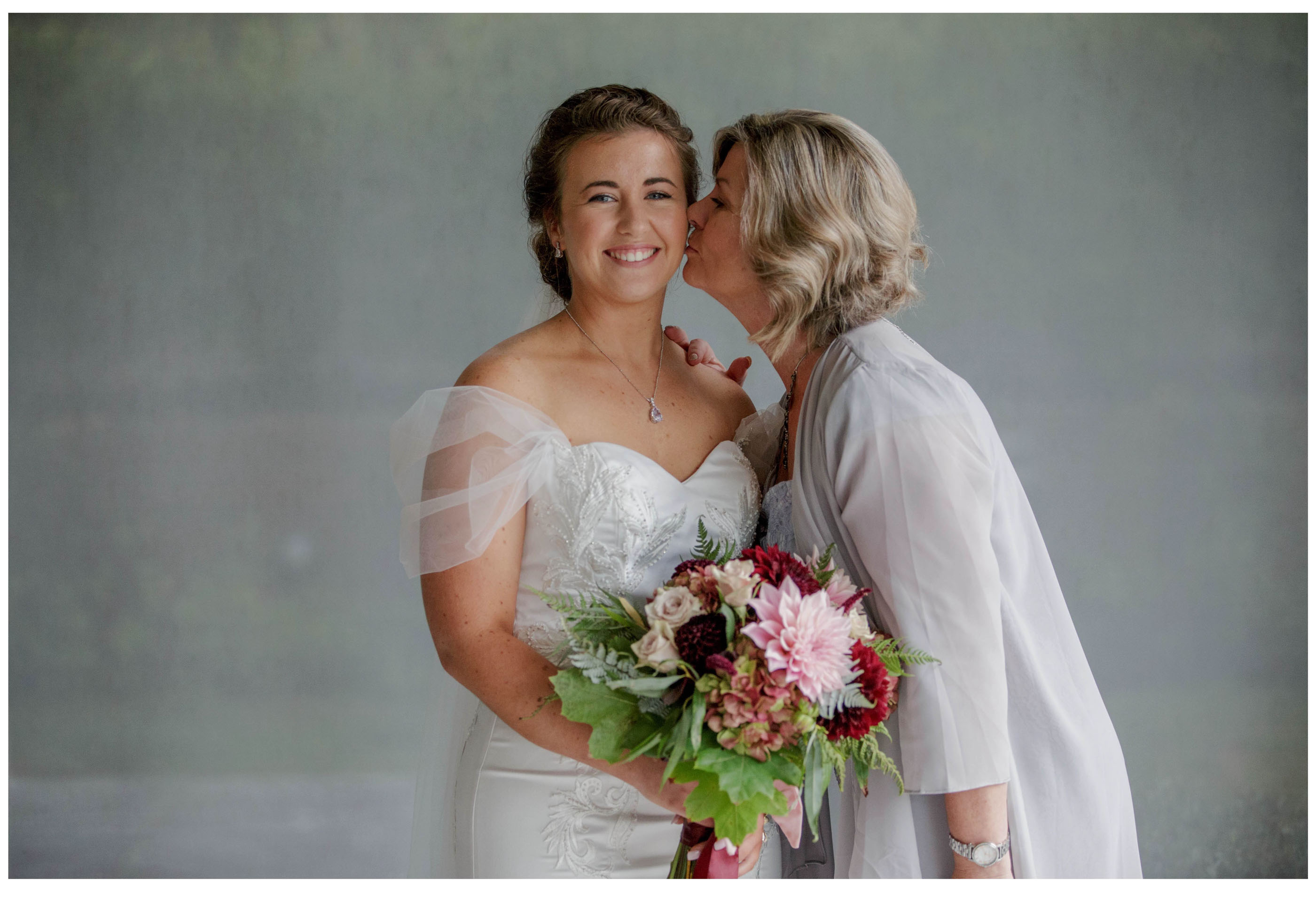 Brides mum kisses bride ready for her wedding in Kumeu