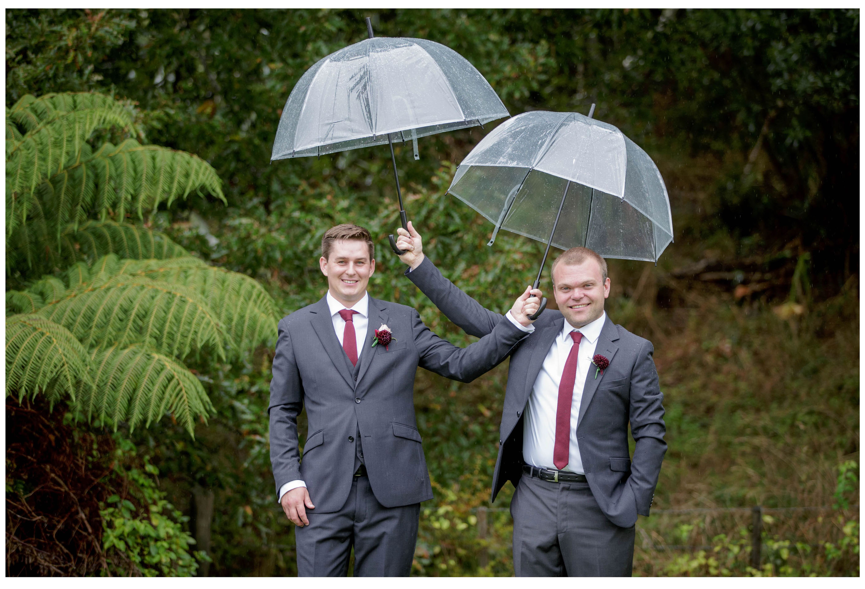 Broom and best man hold umbrellas up above their heads on rainy wedding day.