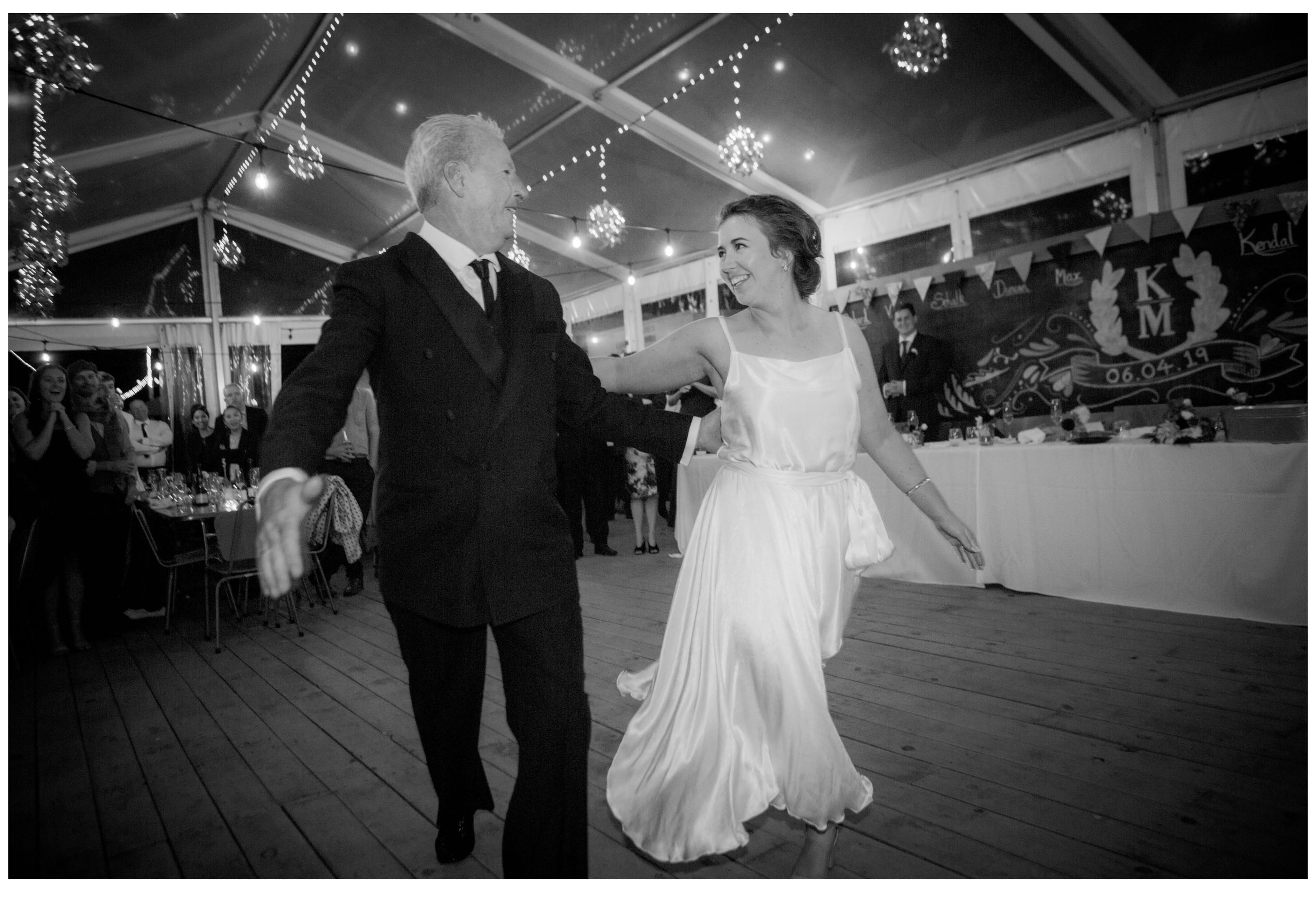 Father and bride dance in marquee wedding reception in Kumeu