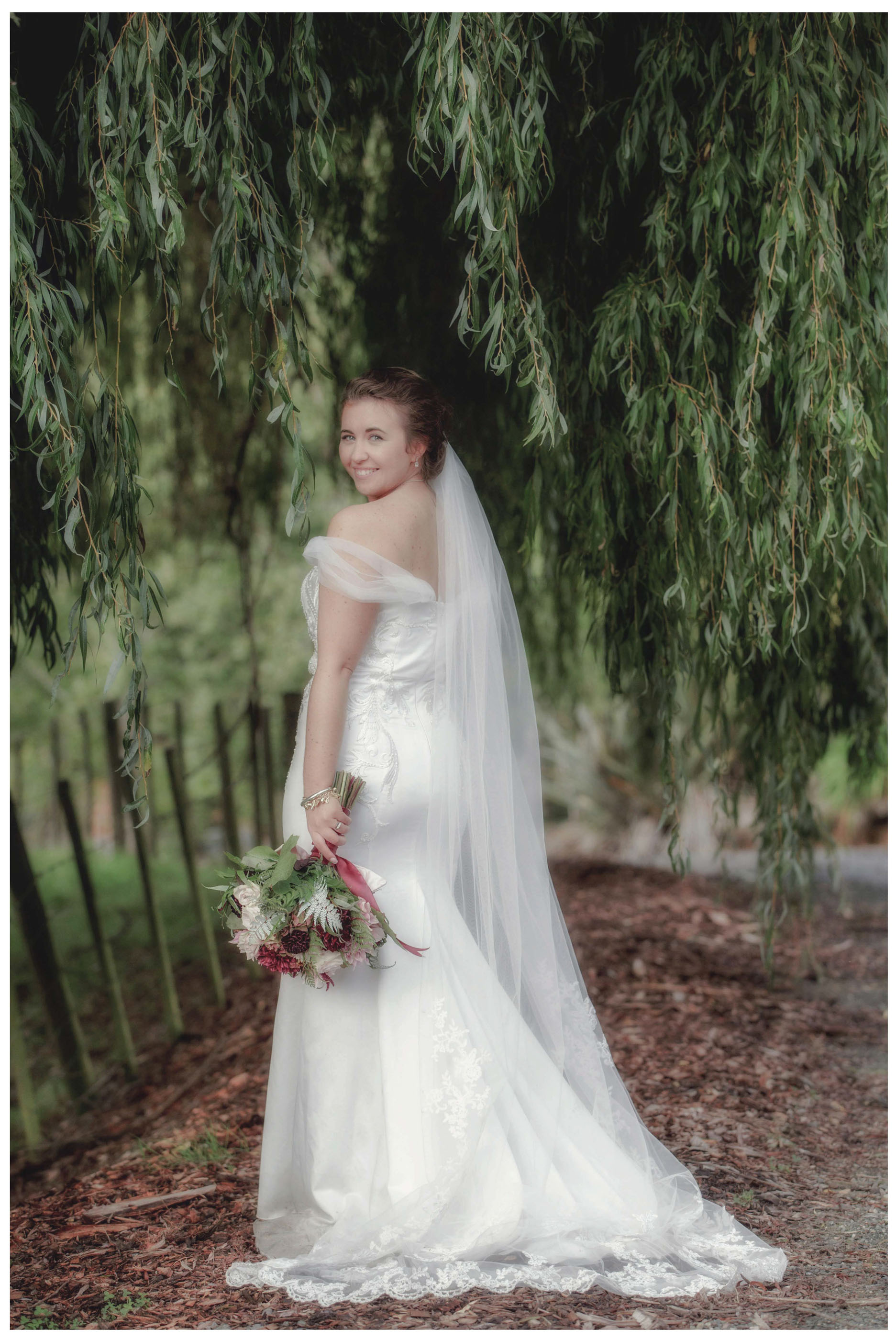 Bride in white wedding dress with her wedding bouquet , Leaf and Honey, Umder a willow tree in Kumeu