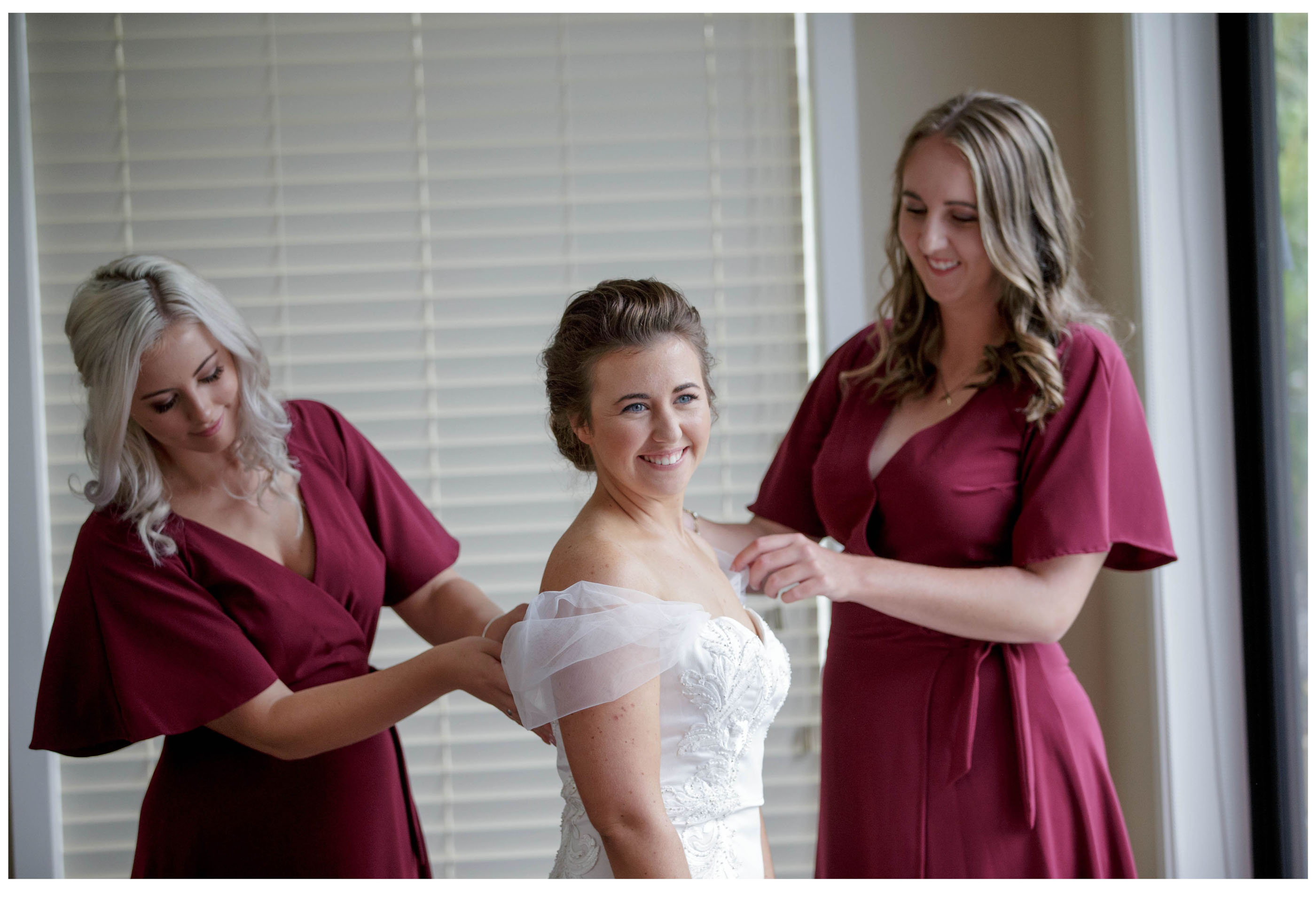 Bride smiles as bridesmaids make sure her dress fits before her wedding in Kumeu