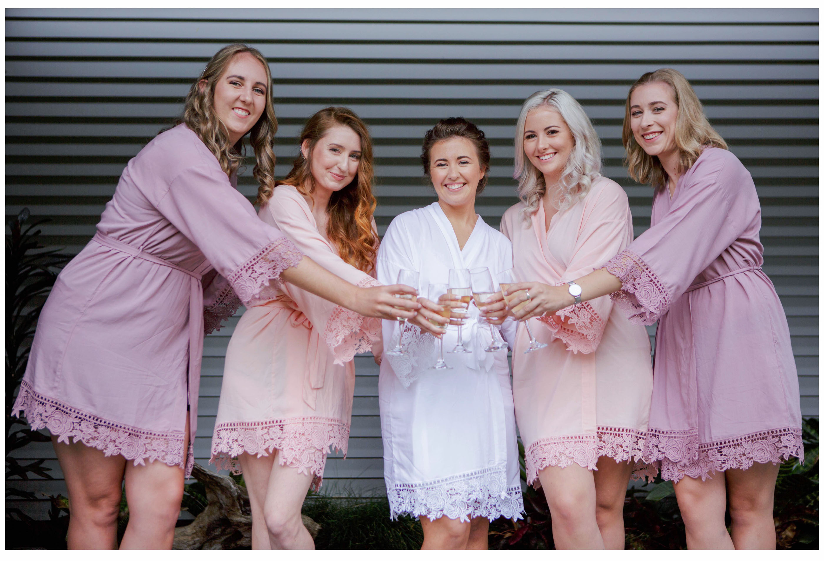 Bride and bridesmaids in dressing robes make champagne toast