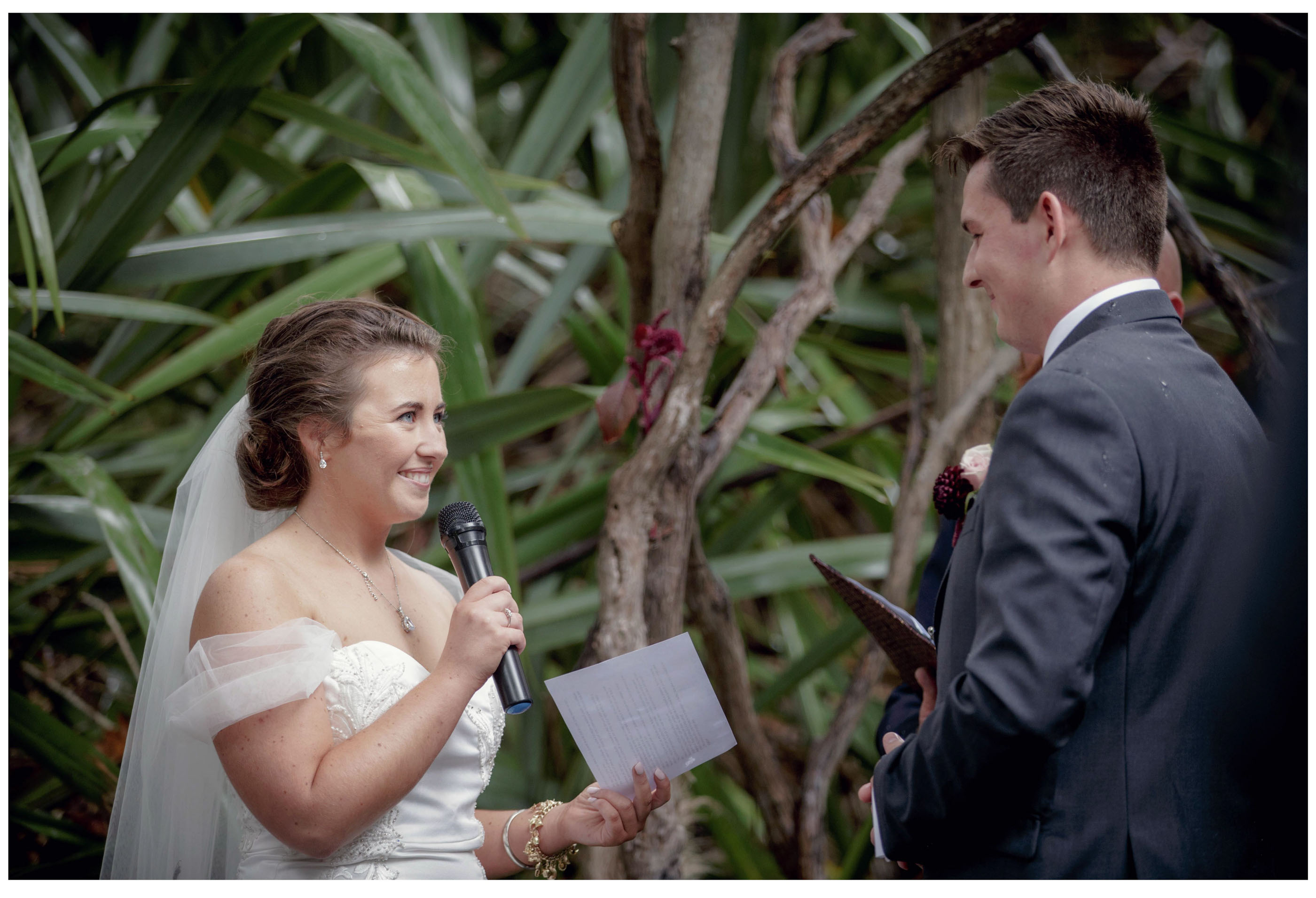 Bride smiles at groom outdoor woodland wedding Kumeu