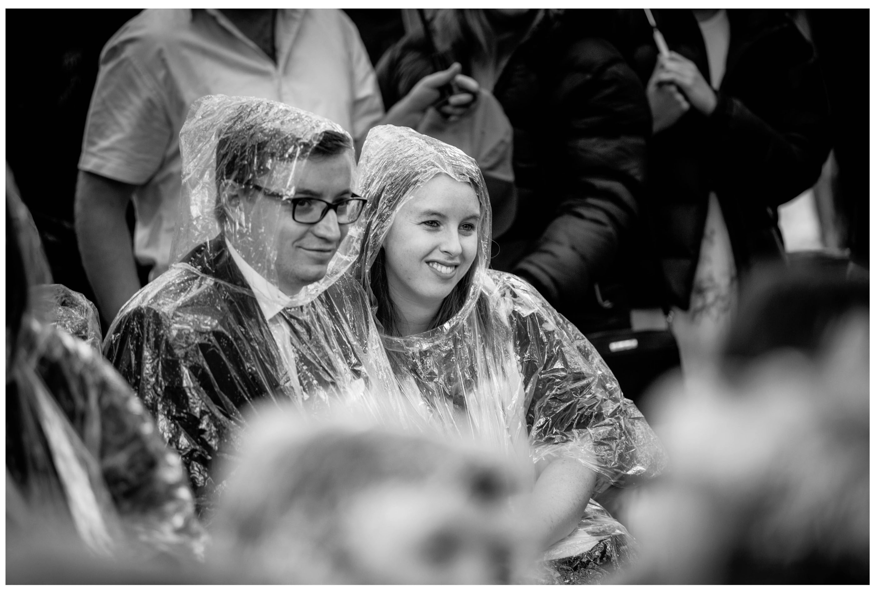 Wedding guests in rain ponchos at rainy outdoor Kumeu wedding