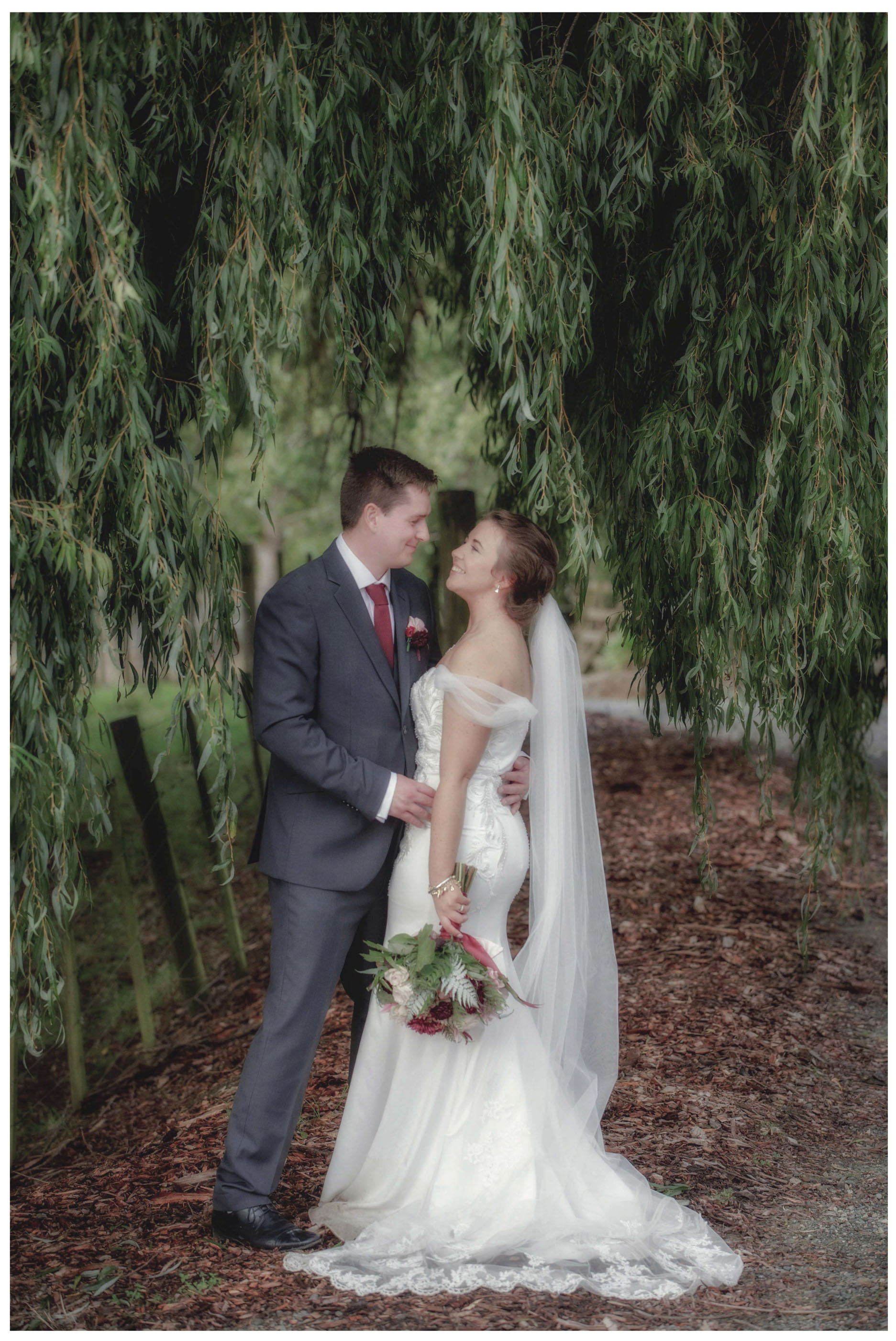 Bride in white wedding dress with flowers kisses groom under willow tree in Kumeu