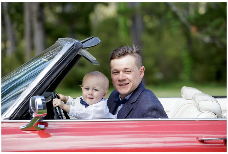 Grom and baby son in weding car