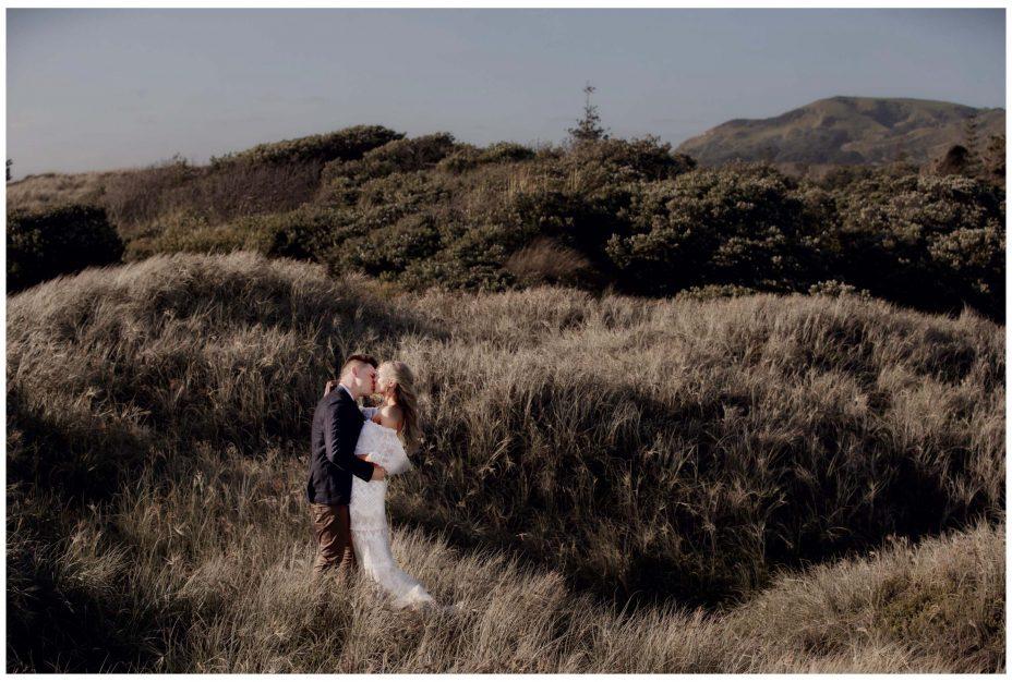 Aussie Bride and groom kiss in sand dunes Murawai Beech, Murawai Beech Wedding photo, romantic wedding photo